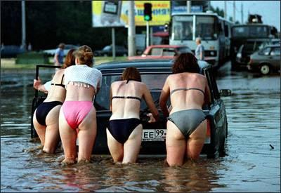Per fortuna che fa caldo. Donne spingono l'auto in bikini